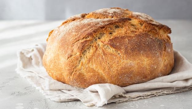 Pain rustique artisanal entier à partir de farine de blé et de seigle sur une serviette en lin