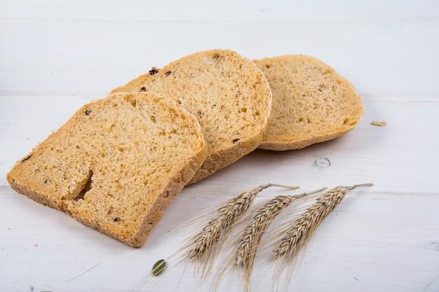 Pain rustique à la levure de blé avec des graines de citrouille sur fond de planche de bois blanc studio photo