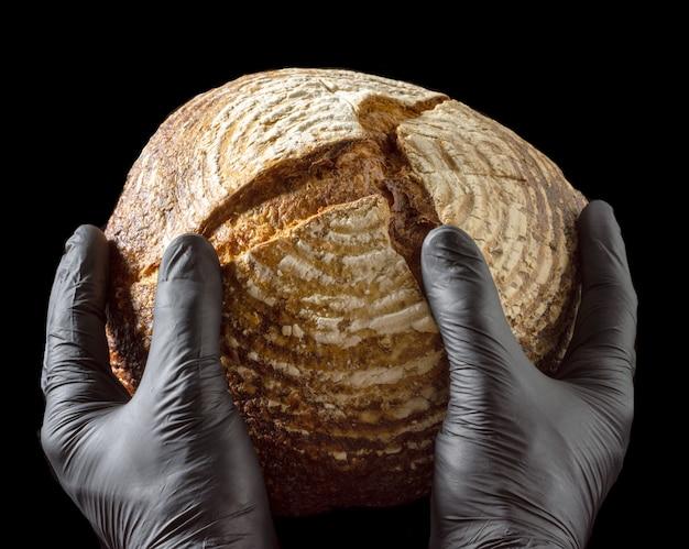 Pain de sarrasin cuit au four dans les mains d'un homme en gants