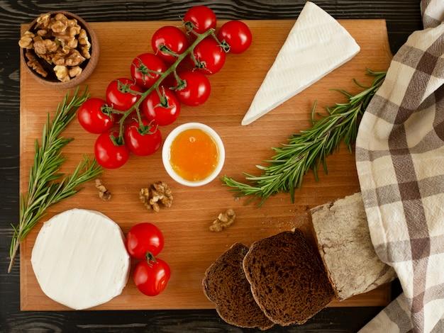 Pain de seigle avec brie et camembert, noix, miel, tomates cerises et romarin