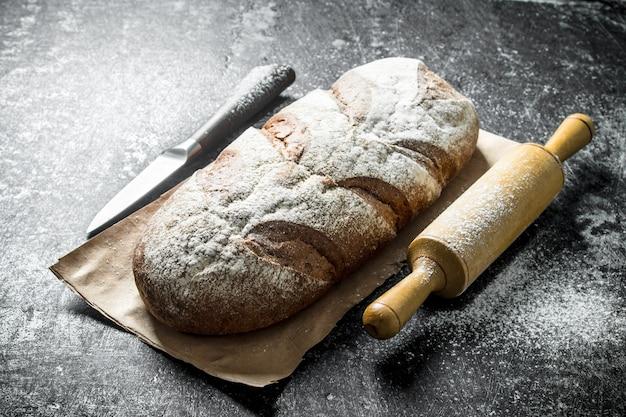 Pain de seigle avec couteau et rouleau à pâtisserie.