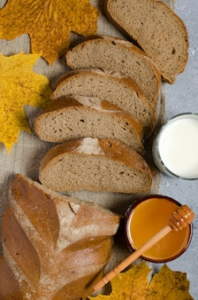Le pain de seigle est coupé en morceaux. miel, lait dans une tasse en verre, feuilles d'érable jaunes.