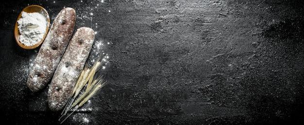 Pain de seigle avec farine et épillets sur une planche en pierre. sur noir rustique