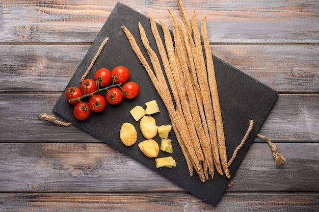 Pain de seigle grissini, tomates cerises, fromage et légumes verts sur une planche en fonte noire sur un fond en bois.