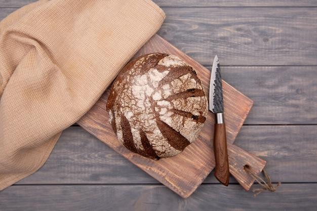 Pain de seigle pain rond sur une planche de bois avec un couteau en bois rustique. vue de dessus.