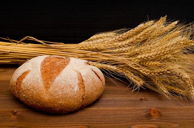 Pain de seigle rond et épis de blé sur une table en bois