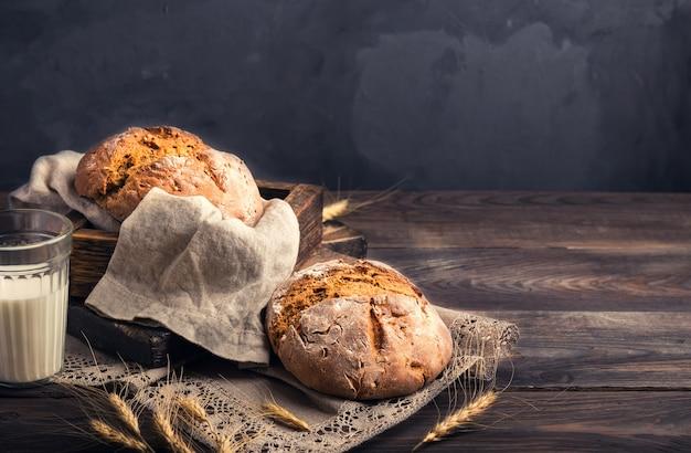 Pain de seigle rustique fait maison avec des graines de coriandre et un verre de lait sur la vieille table en bois. nature morte de la nourriture rurale.
