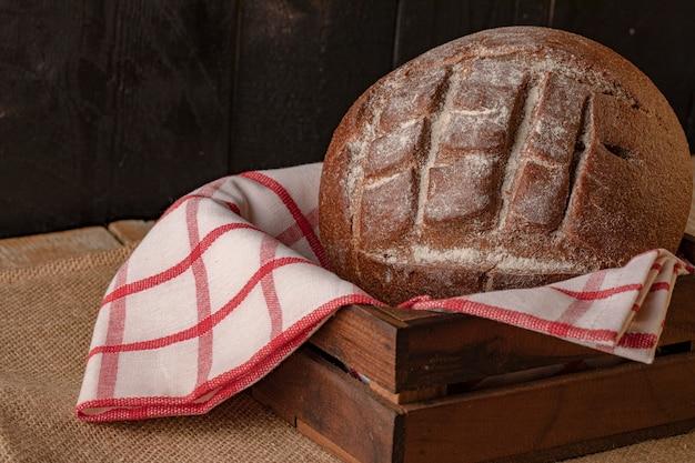 Un pain de seigle sur une serviette à carreaux à l'intérieur du panier en bois.