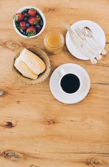 Pain; tasse à café; confiture; baies fraîches et couverts sur plaque sur fond en bois