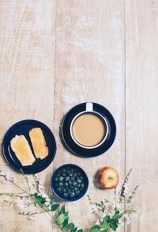 Pain toasté; myrtilles; pomme et tasse de café sur fond texturé en bois