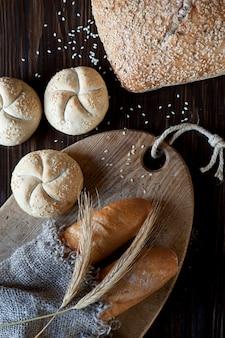 Pain traditionnel fraîchement cuit et épis de blé sur la table en bois. concept de récolte et de boulangerie.
