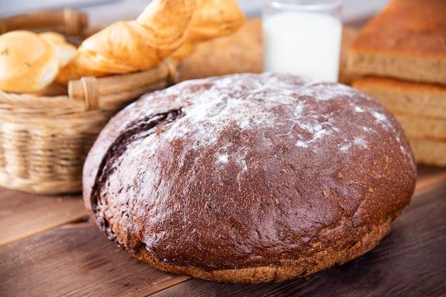 Pain traditionnel noir fait maison avec d'autres types de produits de boulangerie, vue de dessus sur une table en bois foncé