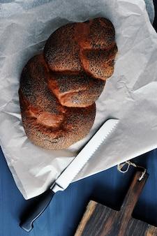 Pain tressé aux graines de pavot sur papier brun avec un couteau à pain