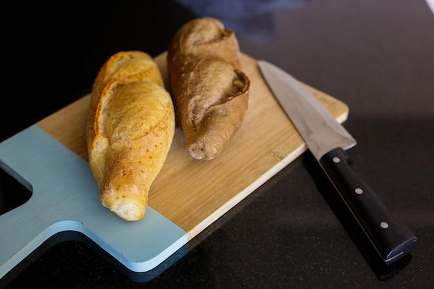 Pain turc frais et couteau sur une planche à découper en bois
