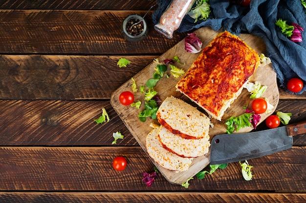 Pain de viande américain avec viande de poulet, citrouille et pois verts. viande de poulet hachée cuite au four. vue de dessus