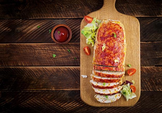 Pain de viande de dinde cuit au four maison savoureux avec du maïs et des tranches de citrouille sur table en bois