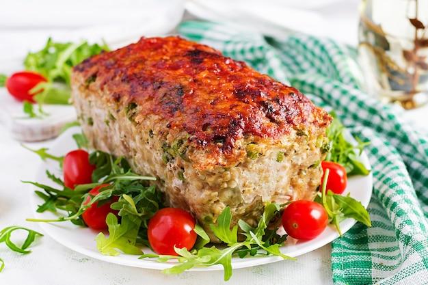 Pain de viande de poulet cuit au four maison savoureux avec des pois verts et des tranches de brocoli sur tableau blanc