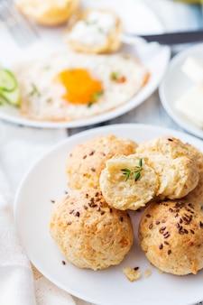 Pains au fromage faits maison avec des graines de lin. petit-déjeuner avec des scones et des œufs au plat.