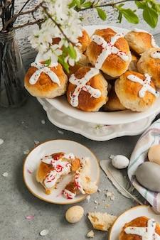 Pains chauds traditionnels de pâques faits maison et oeufs peints sur une surface grise