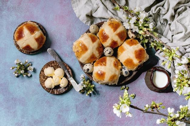 Pains chauds traditionnels de pâques faits maison sur plaque en céramique avec des branches de cerisier en fleurs, beurre, cruche de lait, textile sur mur de texture bleu