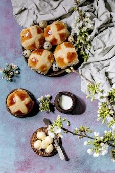 Pains chauds traditionnels de pâques faits maison sur plaque en céramique avec des branches de cerisier en fleurs, beurre, cruche de lait