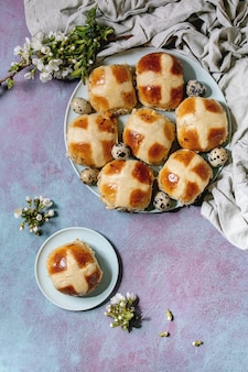 Pains chauds traditionnels de pâques faits maison sur plaque en céramique avec des branches de cerisier en fleurs, oeufs de caille, textile sur mur de texture bleu