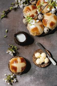 Pains chauds traditionnels de pâques faits maison sur plaque en céramique avec des branches de cerisier en fleurs