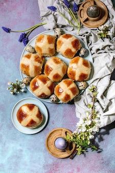 Pains chauds traditionnels de pâques faits maison sur plaque en céramique avec fleurs muscari, branches de fleurs, œufs de caille, textile
