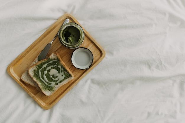Pains et confiture de matcha au thé vert sur une assiette en bois.