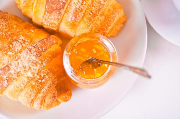 Pains croissants frais, oranges, confiture d'orange. concept de petit déjeuner.