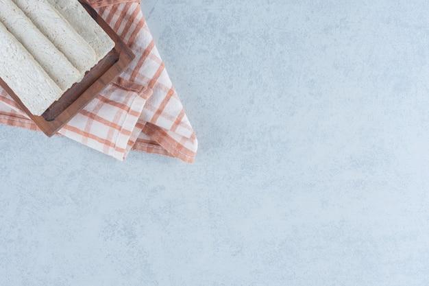 Pains croustillants dans la planche dans la serviette sur le marbre.