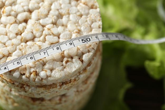 Pains croustillants de riz rond avec ruban à mesurer et laitue, gros plan