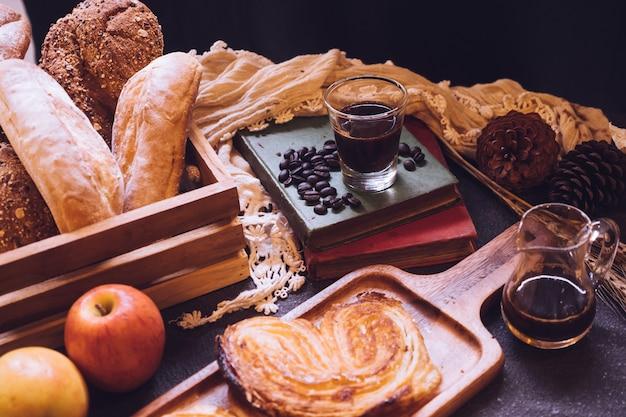 Pains cuits au four, pommes et café sur une table.
