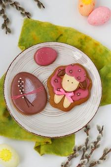 Pains d'épices de pâques sous la forme de moutons et d'oeufs mignons dans une assiette sur fond blanc, vue du dessus, le concept de la fête de l'église de printemps