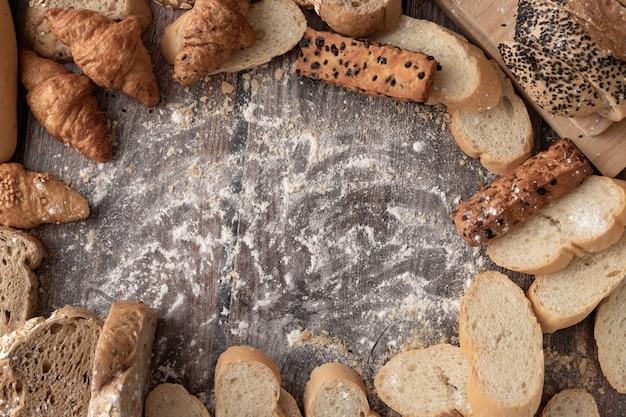 Pains et farine à pâtisserie sur une table en bois et espace de copie
