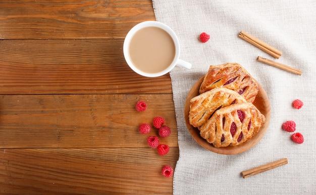 Pains de pâte feuilletée avec de la confiture de fraises sur un fond en bois avec du lin textile et une tasse de café
