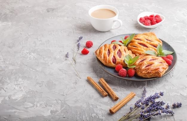 Pains de pâte feuilletée avec de la confiture de fraises sur une plaque en céramique bleue sur fond de béton gris