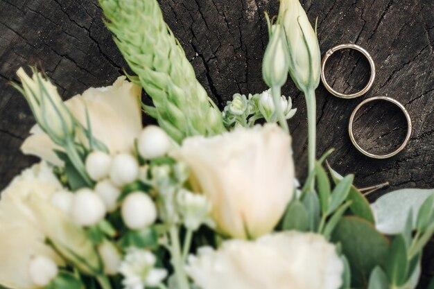Paire ou alliances sur bouquet de fleurs se concentrer sur les anneaux