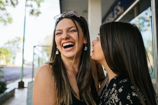 Paire d'amis mignons riant dans la ville.