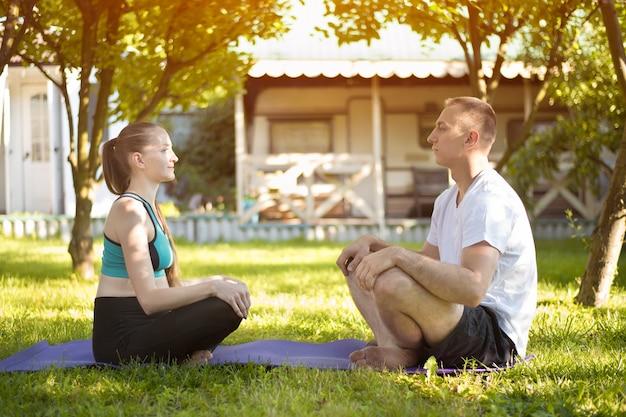 Paire d'amoureux assis sur un tapis de yoga et se regardant.