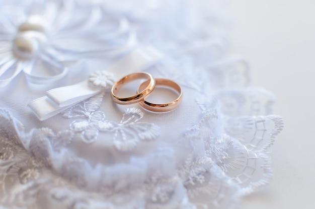 Paire de bagues traditionnelles de mariage en or sur un coussin de dentelle blanche