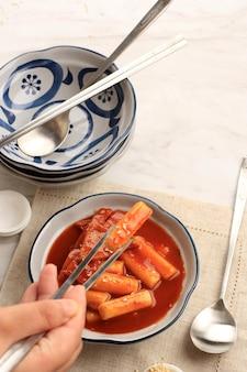 Une paire de baguettes pick tteokbokki dans un bol, une cuisine de rue populaire en corée du sud