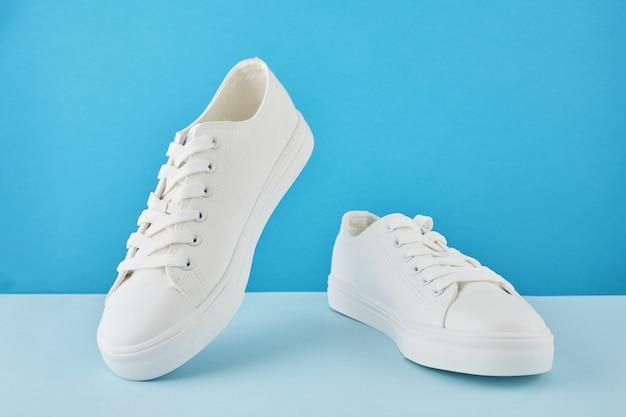 Paire de baskets blanches élégantes à la mode, chaussures de sport de course sur un bleu pastel