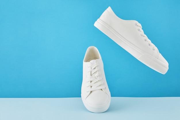 Paire de baskets blanches élégantes à la mode, chaussures de sport de course sur fond bleu pastel.