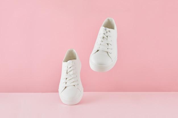 Paire de baskets blanches élégantes à la mode, chaussures de sport de course sur fond rose pastel.