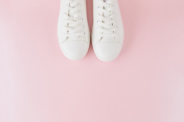 Paire de baskets blanches élégantes à la mode, chaussures de sport de course sur un rose pastel