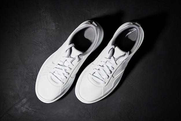 Paire de baskets blanches sur fond noir