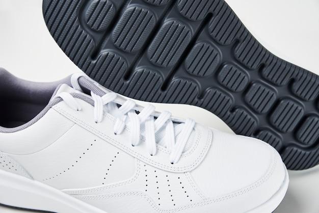 Paire de baskets blanches mâles sur blanc. chaussures de sport élégantes de mode, gros plan