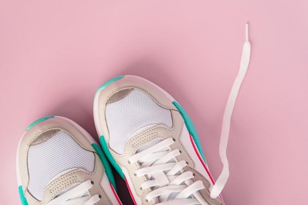 Une paire de baskets blanches sur un mur rose