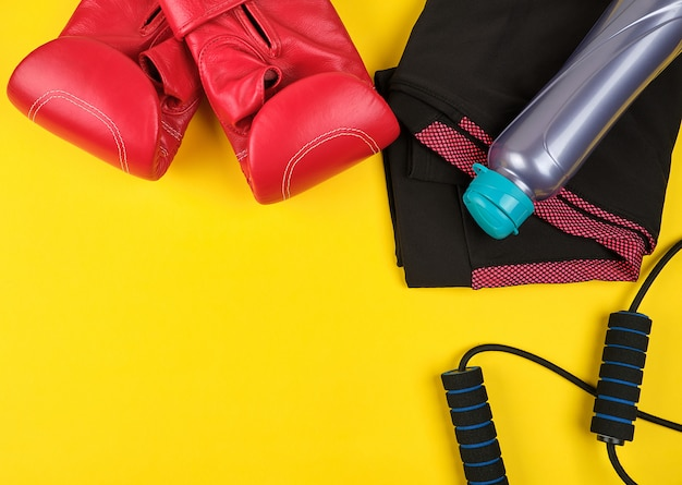 Paire de baskets bleues, de gants de boxe en cuir rouge et d'une corde à sauter noire